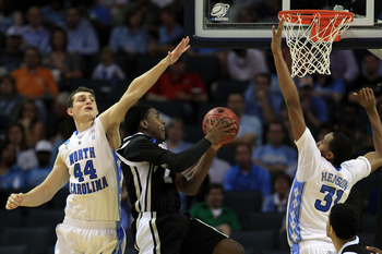 CHARLOTTE, NC - MARCH 18:  Jamal Olasewere #1 of the Long Island Blackbirds goes up for a shot between Tyler Zeller #44 and John Henson #31 of the North Carolina Tar Heels in the second half during the second round of the 2011 NCAA men's basketball tourna