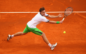 MONACO - APRIL 12:  Ernests Gulbis of Latvia plays a forehand in his match against Milos Raonic of Canada during Day Three of the ATP Masters Series Tennis at the Monte Carlo Country Club on April 12, 2011 in Monte Carlo, Monaco.  (Photo by Julian Finney/