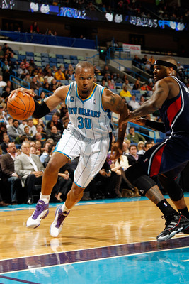 NEW ORLEANS, LA - DECEMBER 26:  David West #30 of the New Orleans Hornets drives the ball around Josh Smith #5 of the Atlanta Hawks at the New Orleans Arena on December 26, 2010 in New Orleans, Louisiana.  The Hornets defeated the Hawks 93-86.  NOTE TO US