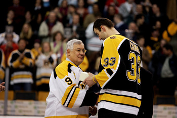 BOSTON - FEBRUARY 13:  Zdeno Chara #33 of the Boston Bruins presents a gift to former Bruins player John Bucyk during the ceremony honoring Bucyk's 50 years with the Bruins organization before the game against the Edmonton Oilers on February 13, 2007 at T