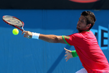MELBOURNE, AUSTRALIA - JANUARY 23:  Fernando Verdasco of Spain plays a backhand in his fourth round match against Tomas Berdych of the Czech Republic during day seven of the 2011 Australian Open at Melbourne Park on January 23, 2011 in Melbourne, Australi