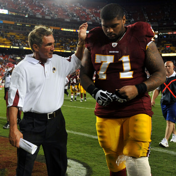 LANDOVER - SEPTEMBER 19:  Trent Williams #71 of the Washington Redskins is consoled by head coach Mike Shanahan during the game against the Houston Texans at FedExField on September 19, 2010 in Landover, Maryland. The Texans defeated the Redskins in overt