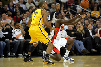 OAKLAND, CA - NOVEMBER 30:  Anthony Morrow #22 of the Golden State Warriors passes the ball from his knees while defended by Dahntay Jones #1 of the Indiana Pacers at Oracle Arena on November 30, 2009 in Oakland, California.  NOTE TO USER: User expressly