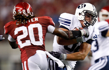 ARLINGTON, TX - SEPTEMBER 05:  Tight end Dennis Pitta #32 of the Brigham Young Cougars runs the ball past Quinton Carter #20 of the Oklahoma Sooners at Cowboys Stadium on September 5, 2009 in Arlington, Texas.  (Photo by Ronald Martinez/Getty Images)