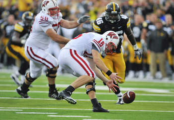 IOWA CITY, IA - OCTOBER 23- Quarterback Scott Tolzien #12 of the Wisconsin Badgers recovers his own fumble as Defensive lineman Christian Ballard #46 of the University of Iowa Hawkeyes defends during the second half of play at Kinnick Stadium on October 2