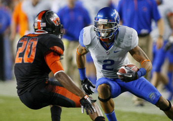 LANDOVER, MD - SEPTEMBER 06:  Wide receiver #2 Austin Pettis of the Boise State Broncos tries to avoid cornerback #21 Rashad Carmichael of the Virginia Tech Hokies at FedExField on September 6, 2010 in Landover, Maryland.  (Photo by Geoff Burke/Getty Imag