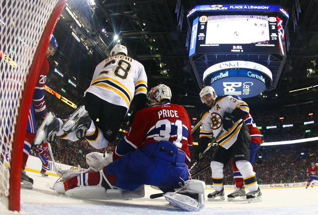 MONTREAL, QC - APRIL 18:  Carey Price #31 of the Montreal Canadiens makes a pad save down low with Mark Recchi #28 of the Boston Bruins running interference at the top of the crease in Game Three of the Eastern Conference Quarterfinals during the 2011 NHL