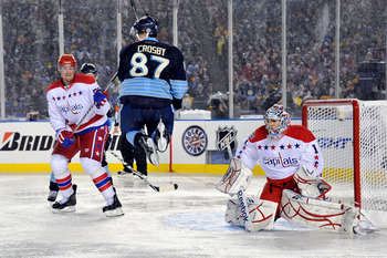 PITTSBURGH, PA - JANUARY 01:  Sidney Crosby #87 of the Pittsburgh Penguins jumps to get out of the way as Semyon Varlamov #1 of the Washington Capitals defends the net during the 2011 NHL Bridgestone Winter Classic at Heinz Field on January 1, 2011 in Pit