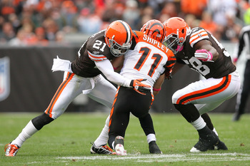 CLEVELAND - OCTOBER 03:  Defenders Eric Wright #21 and Marcus Benard #58 of the Cleveland Browns tackle wide receiver Jordan Shipley #11 of the Cincinnati Bengals at Cleveland Browns Stadium on October 3, 2010 in Cleveland, Ohio.  (Photo by Matt Sullivan/