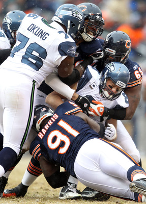 CHICAGO, IL - JANUARY 16:  Quarterback Matt Hasselbeck #8 of the Seattle Seahawks is sacked by three members of the Chicago Bears defense in the first half during the 2011 NFC divisional playoff game at Soldier Field on January 16, 2011 in Chicago, Illino