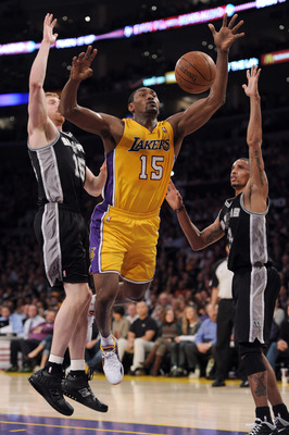 LOS ANGELES, CA - APRIL 12:  Ron Artest #15 of the Los Angeles Lakers is fouled as he attempts a shot in front of Matt Bonner #15 and George Hill #3 of the San Antonio Spurs at Staples Center on April 12, 2011 in Los Angeles, California.  NOTE TO USER: Us