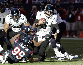 HOUSTON - JANUARY 02:  Quarterback Trent Edwards #5 of the Jacksonville Jaguars is sacked by Troy Nolan #33 of the Houston Texans and Tim Jamison at Reliant Stadium on January 2, 2011 in Houston, Texas.  (Photo by Bob Levey/Getty Images)