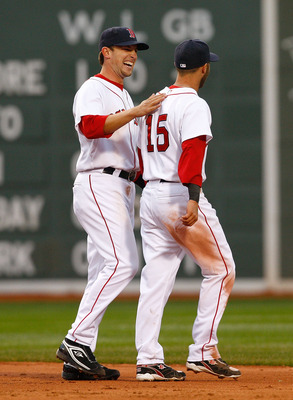 BOSTON - APRIL 7: Jed Lowrie #12 and Justin Pedroia #15 of the Boston Red Sox celebrate after defeating the Tampa Bay Rays, 5-3, at Fenway Park April 7, 2009 in Boston, Massachusetts. (Photo by Jim Rogash/Getty Images)