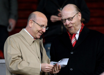 MANCHESTER, ENGLAND - APRIL 12:  Manchester United Directors Joel and Avram Glazer (R) check the team sheet prior to the UEFA Champions League Quarter Final second leg match between Manchester United and Chelsea at Old Trafford on April 12, 2011 in Manche