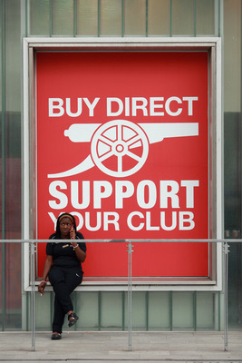 LONDON, ENGLAND - APRIL 11:  A woman sits in front of the club shop at Arsenal Football Club's Emirates Stadium on April 11, 2011 in London, England. American businessman Stan Kroenke's company 'Kroenke Sports Enterprises' has increased its shareholding i