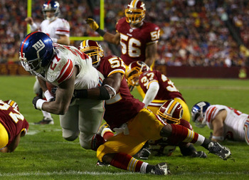 LANDOVER, MD - JANUARY 02: Brandon Jacobs #27 of the New York Giants drags Washington Redskins linebacker Rocky McIntosh into the end zone while scoring a touchdown during their game at FedEx Field on January 2, 2011 in Landover, Maryland.  (Photo by Win