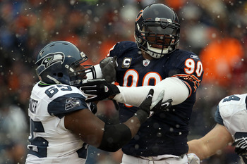 CHICAGO, IL - JANUARY 16:  Julius Peppers #90 of the Chicago Bears is blocked by Chris Spencer #65 of the Seattle Seahawks in the 2011 NFC divisional playoff game at Soldier Field on January 16, 2011 in Chicago, Illinois.  (Photo by Jonathan Daniel/Getty