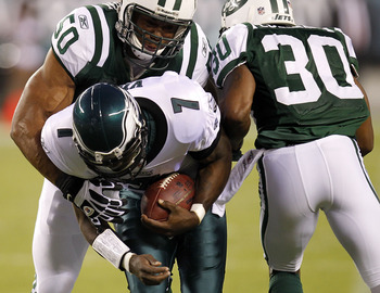 PHILADELPHIA - SEPTEMBER 02:  Michael Vick #7 of the Philadelphia Eagles is tackled by Vernon Gholston #50 and Drew Coleman #30 of the New York Jets during a preseason game at Lincoln Financial Field on September 2, 2010 in Philadelphia, Pennsylvania.  (P