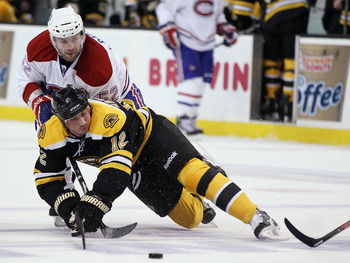 BOSTON, MA - APRIL 16:  Tomas Kaberle #12 of the Boston Bruins is shoved by Mathieu Darche #52 of the Montreal Canadiens in Game Two of the Eastern Conference Quarterfinals during the 2011 NHL Stanley Cup Playoffs at TD Garden on April 16, 2011 in Boston,