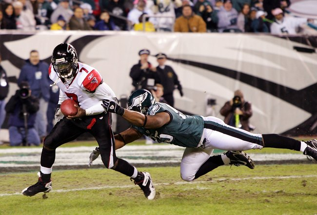 PHILADELPHIA - DECEMBER 31:  Michael Vick #7 of the Atlanta Falcons eludes a tackle by Jerome McDougle #95 of the Philadelphia Eagles in NFL action December 31, 2006 at Lincoln Financial Field in Philadelphia, Pennsylvania. The Eagles won 24-17.  (Photo b