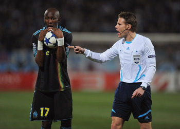 MARSEILLE, FRANCE - FEBRUARY 23:  Stephane Mbia of Marseille exchanges words with referee Felix Brych of Germany during the UEFA Champions League round of 16 first leg match between Marseille and Manchester United at the Stade Velodrome on February 23, 20