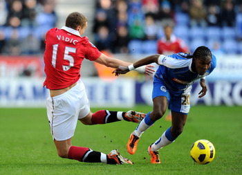 WIGAN, ENGLAND - FEBRUARY 26:  Hugo Rodallega of Wigan Athletic tangles with Nemanja Vidic of Manchester United during the Barclays Premier League match between Wigan Athletic and Manchester United at the DW Stadium on February 26, 2011 in Wigan, England.