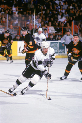 INGLEWOOD, CA - 1990:  Forward Dave Taylor #18 of the Los Angeles Kings skates with the puck against the Vancouver Canucks during the 1990-91 season at the Great Western Forum in Inglewood, California.  (Photo by Ken Levine/Getty Images)