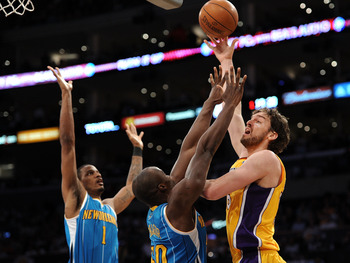 LOS ANGELES, CA - APRIL 20:  Pau Gasol #16 of the Los Angeles Lakers shoots over Emeka Okafor #50 and Trevor Ariza #1 of the New Orleans Hornets in the first quarter in Game Two of the Western Conference Quarterfinals in the 2011 NBA Playoffs on April 20,