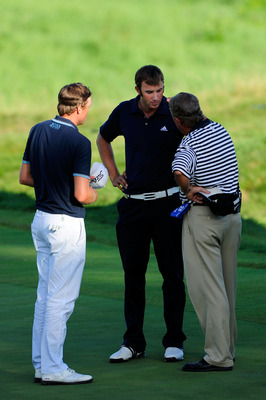 KOHLER, WI - AUGUST 15:  A PGA of America rules official chats with Dustin Johnson (R) on the 18th green as Nick Watney (L) looks on during the final round of the 92nd PGA Championship on the Straits Course at Whistling Straits on August 15, 2010 in Kohle