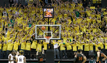 EUGENE, OR - JANUARY 13:  Members of the 'Pit Crew' wave their hands as Maurice Jones #10 of the USC Trojans shoots a free against the Oregon Ducks during the grand opening of the Matthew Knight Arena on January 13, 2011 at Matthew Knight Arena in Eugene,