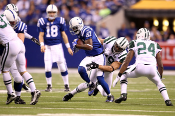 INDIANAPOLIS, IN - JANUARY 08:  Reggie Wayne #87 of the Indianapolis Colts is tackled as he makes a reception against Jason Taylor #99 and Darrelle Revis #24 of the New York Jets during their 2011 AFC wild card playoff game at Lucas Oil Stadium on January