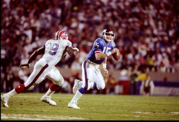 27 Jan 1991: Quarterback Jeff Hostetler of the New York Giants (right) moves the ball as Buffalo Bills defensive lineman Bruce Smith chases him during Super Bowl XXV at Tampa Stadium in Tampa, Florida. The Giants won the game, 20-19.