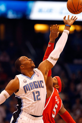 ORLANDO, FL - APRIL 19:  Dwight Howard #12 of the Orlando Magic wins the opening tipoff over Josh Smith of the Atlanta Hawks during Game Two of the Eastern Conference Quarterfinals of the 2011 NBA Playoffs on April 19, 2011 at the Amway Arena in Orlando,