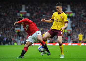 MANCHESTER, ENGLAND - MARCH 12:  Rafael Da Silva of Manchester United and Laurent Koscielny of Arsenal battle for the ball during the FA Cup sponsored by E.On Sixth Round match between Manchester United and Arsenal at Old Trafford on March 12, 2011 in Man