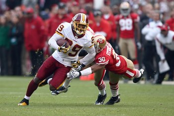 SAN FRANCISCO - DECEMBER 28:  Santana Moss #89 of the Washington Redskins carries the ball as he evades Donald Strickland #30 of the San Fransisco 49ers at Candlestick Park on December 28, 2008 in San Francisco, California. (Photo by: Jonathan Ferrey/Gett