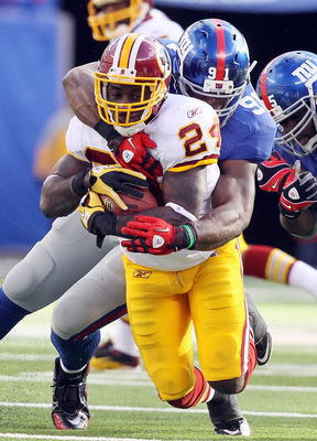 EAST RUTHERFORD, NJ - DECEMBER 05:  James Davis #24 of the Washington Redskins is tackled by Justin Tuck #91 of the New York Giants on December 5, 2010 at the New Meadowlands Stadium in East Rutherford, New Jersey.  (Photo by Jim McIsaac/Getty Images)