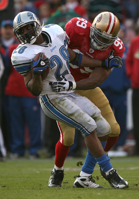 SAN FRANCISCO - DECEMBER 27:  Manny Lawson #99 of the San Francisco 49ers tackles Maurice Morris #28 of the Detroit Lions during an NFL game at Candlestick Park on December 27, 2009 in San Francisco, California.  (Photo by Jed Jacobsohn/Getty Images)