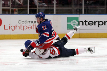 NEW YORK, NY - APRIL 20:  Derek Stepan #21 of the New York Rangers falls to the ice as he was tripped up by Mike Green #52 of the Washington Capitals in Game Four of the Eastern Conference Quarterfinals during the 2011 NHL Stanley Cup Playoffs at Madison