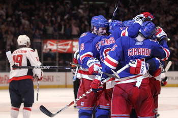 NEW YORK, NY - APRIL 20:  The New York Rangers celebrate after Brandon Dubinsky #17 scored a second period goal as Nicklas Backstrom #19 of the Washington Capitals skates off in Game Four of the Eastern Conference Quarterfinals during the 2011 NHL Stanley