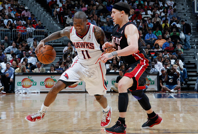 ATLANTA, GA - APRIL 11:  Jamal Crawford #11 of the Atlanta Hawks drives against Mike Bibby #0 of the Miami Heat at Philips Arena on April 11, 2011 in Atlanta, Georgia.  NOTE TO USER: User expressly acknowledges and agrees that, by downloading and/or using