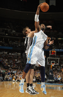 DENVER, CO - MARCH 23:  Nene #31 of the Denver Nuggets grabs a rebound away from Tiago Splitter #22 at the Pepsi Center on March 23, 2011 in Denver, Colorado. The Nuggets defeated the Spurs 115-112. NOTE TO USER: User expressly acknowledges and agrees tha