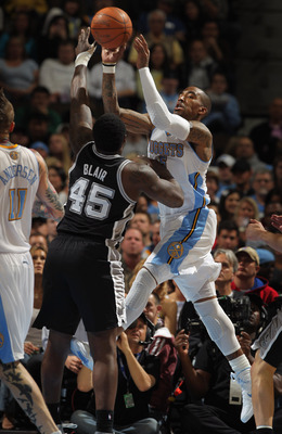 DENVER, CO - MARCH 23:  J.R. Smith #5 of the Denver Nuggets passes the ball against the defense of DeJuan Blair #45 of the San Antonio Spurs at the Pepsi Center on March 23, 2011 in Denver, Colorado. The Nuggets defeated the Spurs 115-112. NOTE TO USER: U