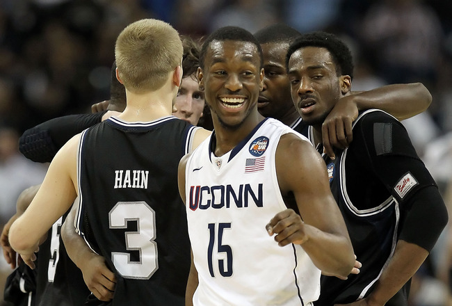 HOUSTON, TX - APRIL 04:  Kemba Walker #15 of the Connecticut Huskies smiles as the Butler Bulldogs huddle during the National Championship Game of the 2011 NCAA Division I Men's Basketball Tournament at Reliant Stadium on April 4, 2011 in Houston, Texas.