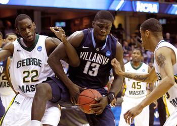 CLEVELAND, OH - MARCH 18: Mouphtaou Yarou #13 of the Villanova Wildcats fights for a loose ball with Mike Morrison #22 of the George Mason Patriots during the second round of the 2011 NCAA men's basketball tournament at Quicken Loans Arena on March 18, 20