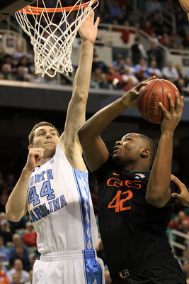 GREENSBORO, NC - MARCH 11:  Reggie Johnson #42 of the Miami Hurricanes shoots against Tyler Zeller #44 of the North Carolina Tar Heels during the first half in the quarterfinals of the 2011 ACC men's basketball tournament at the Greensboro Coliseum on Mar