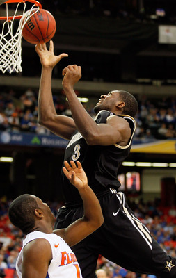 ATLANTA, GA - MARCH 12:  Festus Ezeli #3 of the Vanderbilt Commodores goes up for a shot against Erving Walker #11 of the Florida Gators during the semifinals of the SEC Men's Basketball Tournament at Georgia Dome on March 12, 2011 in Atlanta, Georgia.  (