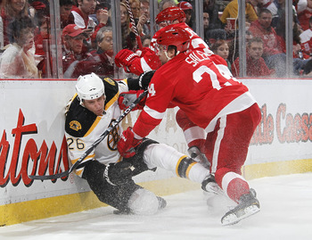 DETROIT, MI - FEBRUARY 13:  Ruslan Salei #24 of the Detroit Red Wings checks Blake Wheeler #26 of the Boston Bruins into the boards on February 13, 2011 at Joe Lewis Arena in Detroit, Michigan. Detroit won the game 4-2.  (Photo by Gregory Shamus/Getty Ima