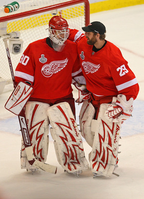 DETROIT - JUNE 06:  Goaltender Chris Osgood #30 of the Detroit Red Wings is congratulated by backup goaltender Ty Conklin #29 after a 5-0 win over the Pittsburgh Penguins in Game Five of the 2009 NHL Stanley Cup Finals at Joe Louis Arena on June 6, 2009 i