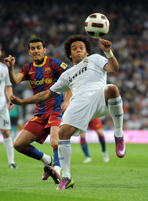 MADRID, SPAIN - APRIL 16:  Marcelo of Real Madrid clears the ball beside Pedro Rodriguez of Barcelona during the La Liga match between Real Madrid and Barcelona at Estadio Santiago Bernabeu on April 16, 2011 in Madrid, Spain.  (Photo by Denis Doyle/Getty
