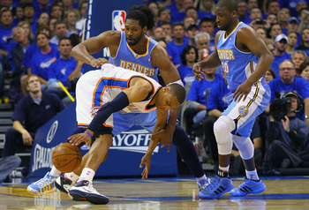 OKLAHOMA CITY, OK - APRIL 20: Russell Westbrook #0 of the Oklahoma City Thunder looses control of the ball against Nene Hilario #31 \and Raymond Felton #20 both of the Denver Nuggets in Game Two of the Western Conference Quarterfinals in the 2011 NBA Play